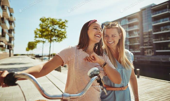 Unbeschwerte Freundinnen zu Fuß mit dem Fahrrad durch die Stadt
