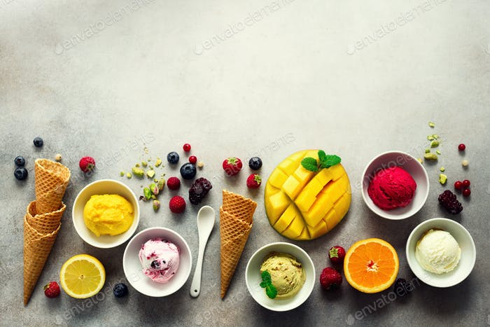 Ice cream balls in bowls, waffle cones, berries, orange, mango, pistachio on grey concrete