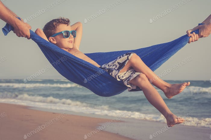 Happy little boy relaxing on the beach at the day time