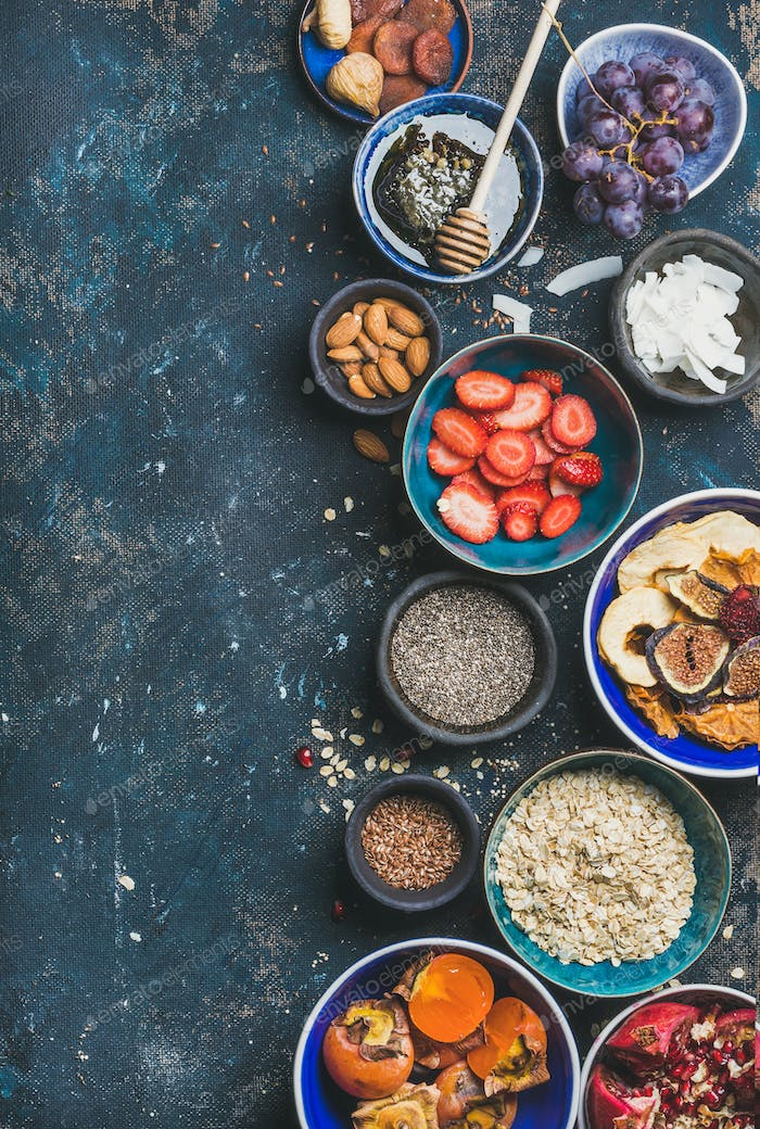 Ingredients for healthy breakfast in bowls over plywood background