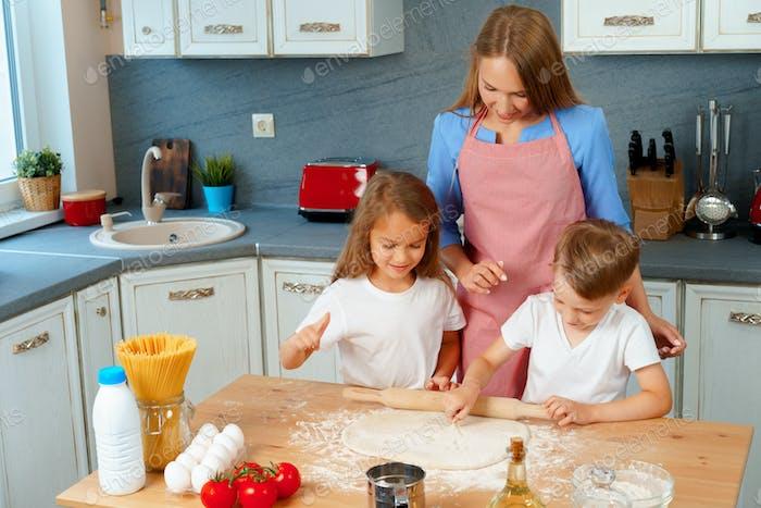 Mujer rubia joven, madre y sus hijos divirtiéndose mientras se cocina la masa