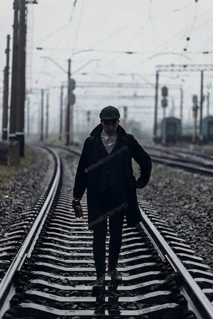 Silhouette von stilvollen Gangster Mann mit Flasche Whisky zu Fuß auf der Eisenbahnstraße
