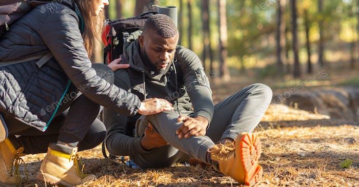Unerkennbare Frau tröstet verletzten schwarzen Kerl, Rucksackreisen zusammen durch Wald