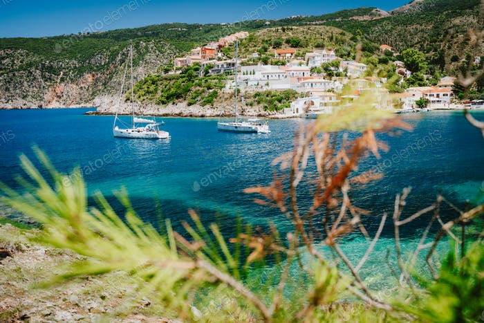 Cozy colorful town Assos. Mediterranean sea and yacht sail boats. Kefalonia Island, Greece
