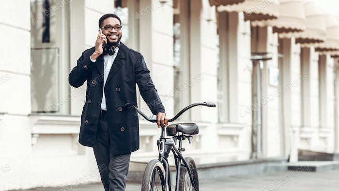 African-american businessman talking on phone, riding bicycle