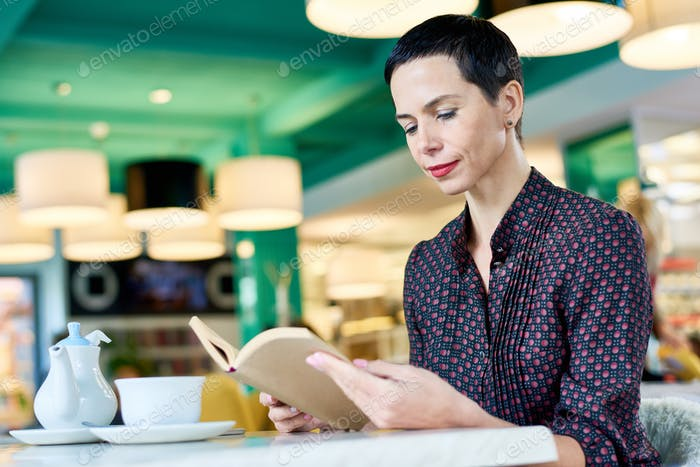 Elegant Woman Reading Book in Cafe