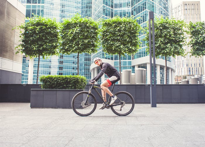 man cyclist in sportswear ride on road in the city