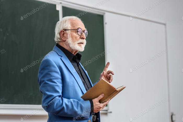 senior lecturer holding book and showing one finger up