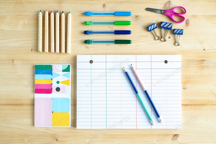 Top view of sheet of paper with lines surrounded by group of office supplies