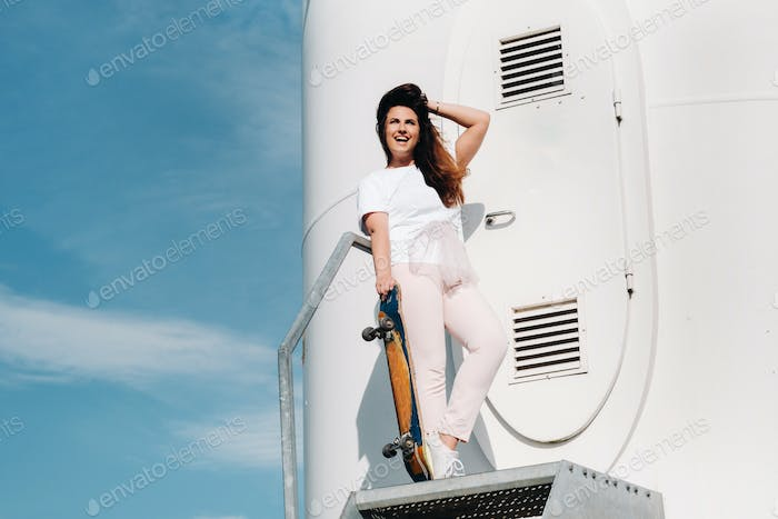 A girl in white clothes with a skate in her hands is photographed near large wind turbines in a