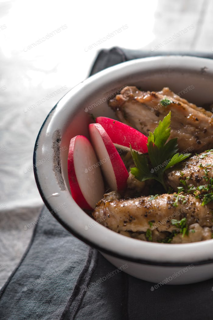 Pilaf with chicken in a metal bowl and radishes closeup