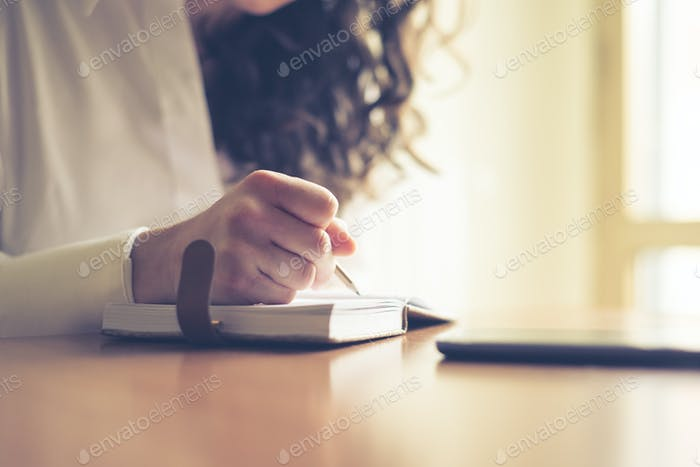 beautiful woman at home writing and working