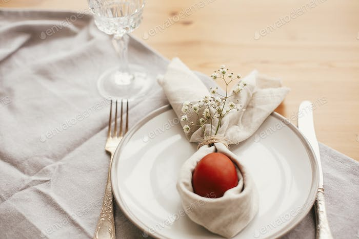 Stylish Easter brunch table setting with egg in easter bunny napkin on  table