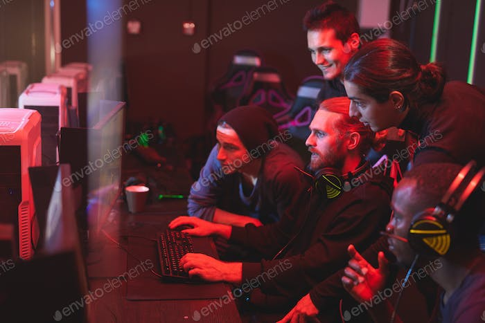 Young men assisting friend to pass video game