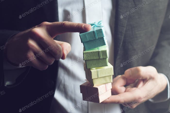 Man holding small gift boxes with his index fingers
