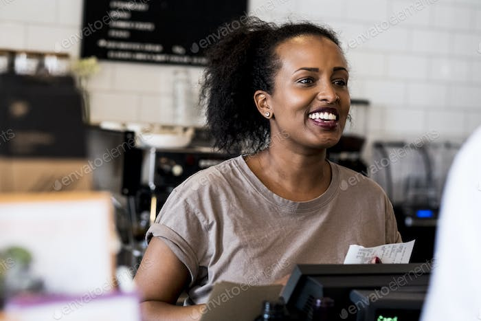 A woman barista smiling in welcome beside the counter in a coffee shop.