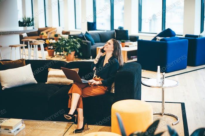 Feliz mujer de negocios hablando por teléfono en la oficina moderna.