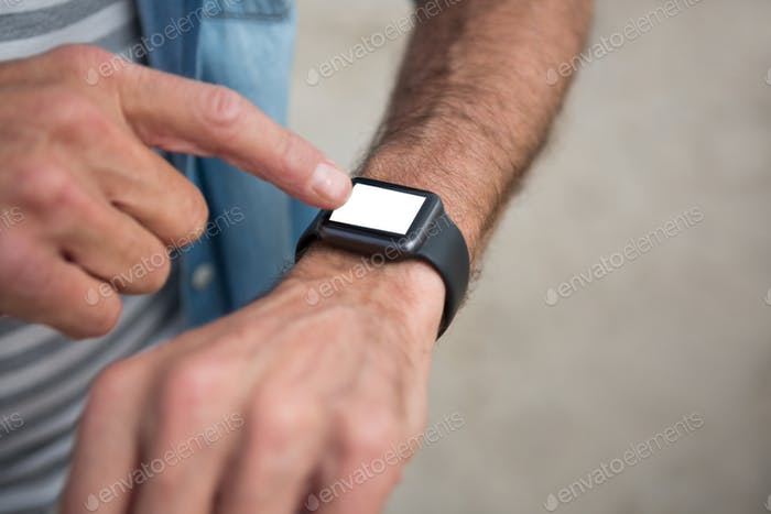 Mid section of man wearing smartwatch on beach
