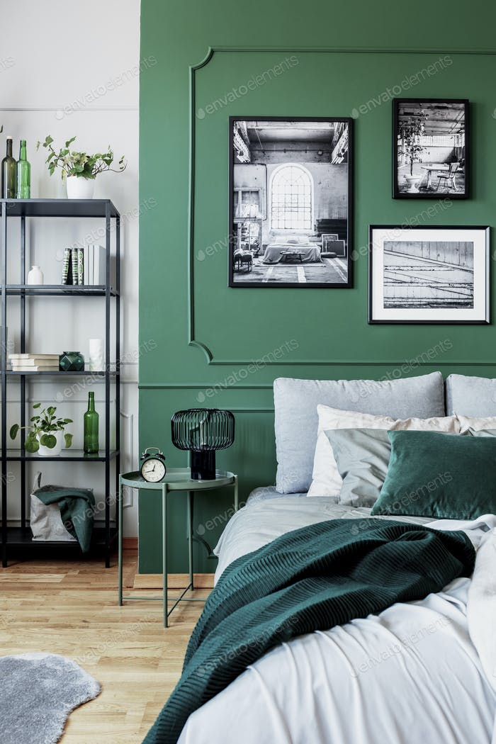 Stylish bedroom interior with double bed and emerald green wall