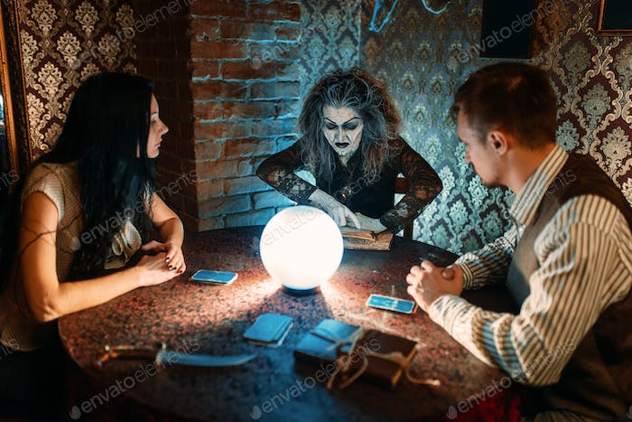 Family and witch at the table with crystal ball