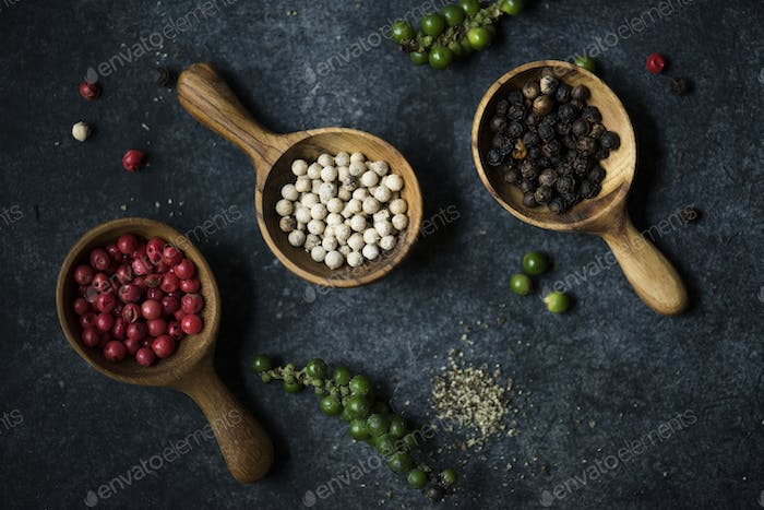Mixed pepper seasoning in wooden spoon