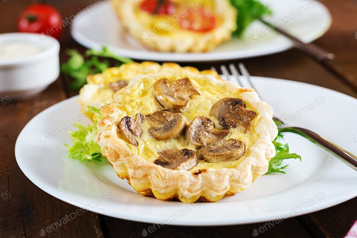 Mushrooms, cheddar tartlets on wooden background. Mini pies. Delicious appetizer, tapas, snack.