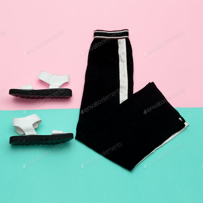 Flat lay fashion set: white sandal shoes with and black pants wi