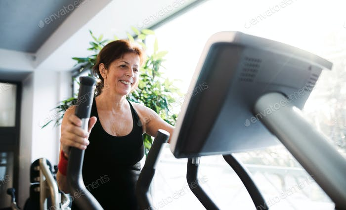 A cheerful female senior in gym doing cardio workout.