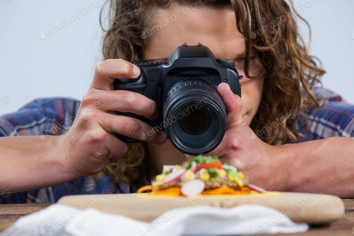 Photographer clicking a picture of food using digital camera