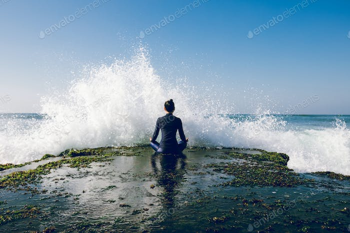 Woman meditation at seaside in front of giant waves