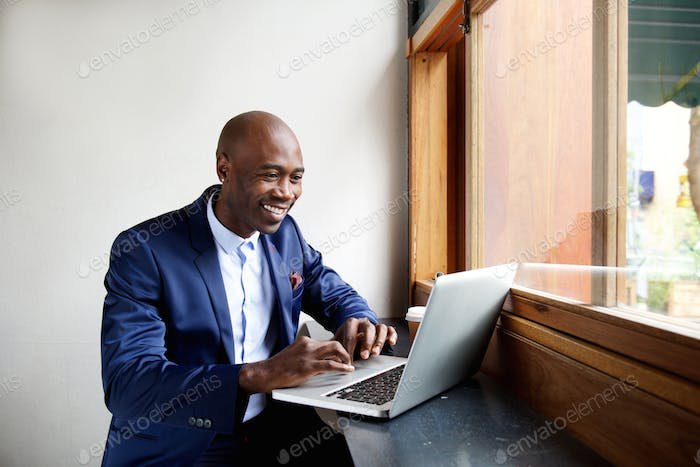 Happy african businessman working on laptop at cafe