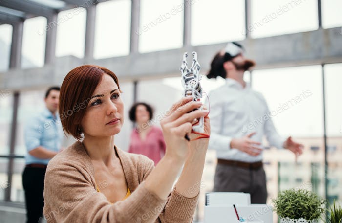 Young businesswoman or scientist with robotic hand standing in office, working.