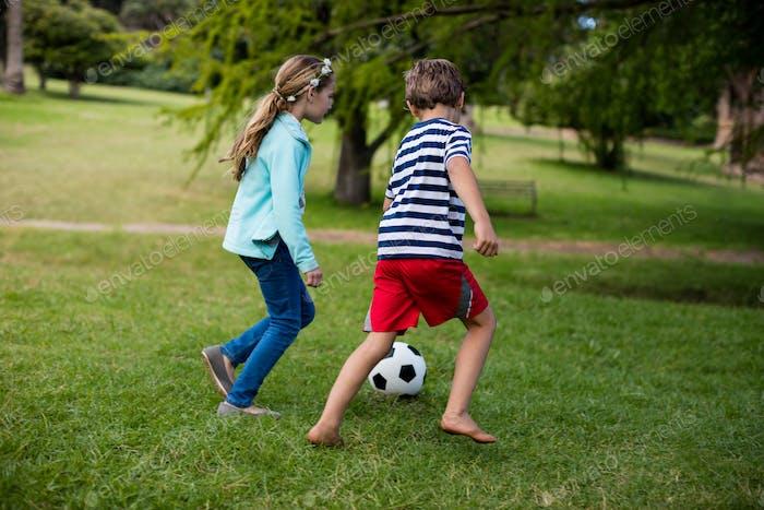 Junge und Mädchen Fußball spielen