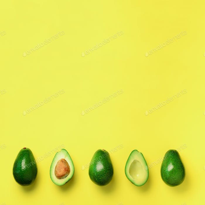 Organic avocado with seed, avocado halves and whole fruits on yellow background. Top view. Square