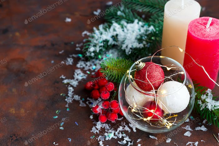 Red and white Christmas ball in a glass jar, color candles, fir branches and berries on a dark stone