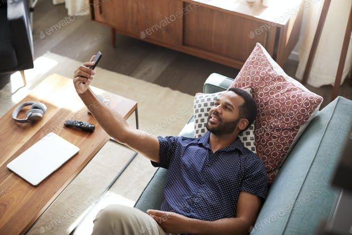 Overhead View Of Man Lying On Sofa At Home Posing For Selfie On Mobile Phone