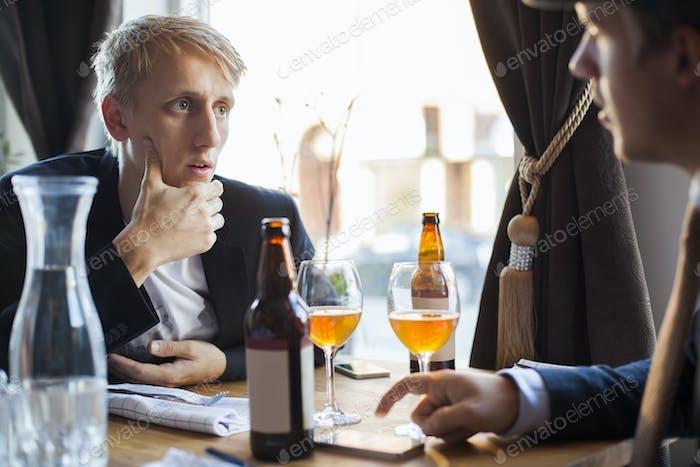 Worried man listening to gay partner in restaurant