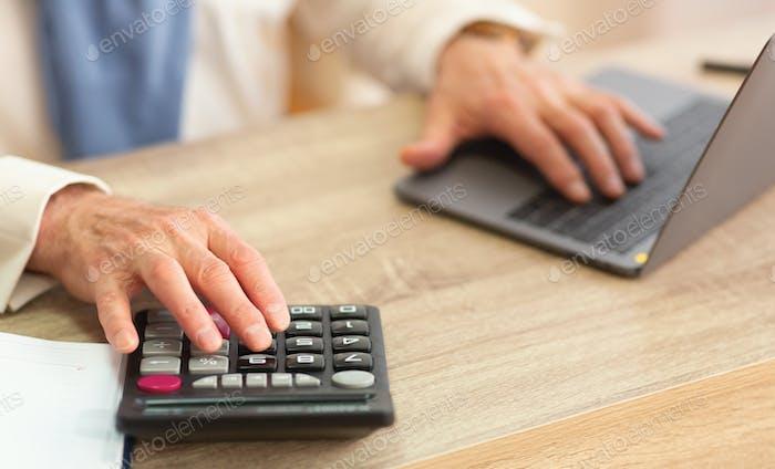 Ältere Mannes Hände mit Taschenrechner und Laptop im Büro