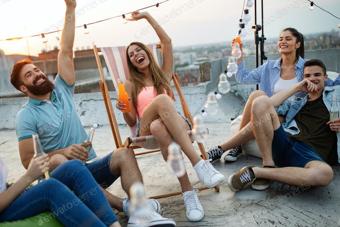 Spending great time with friends. Young friends chatting and havinf fun on the roof of the building