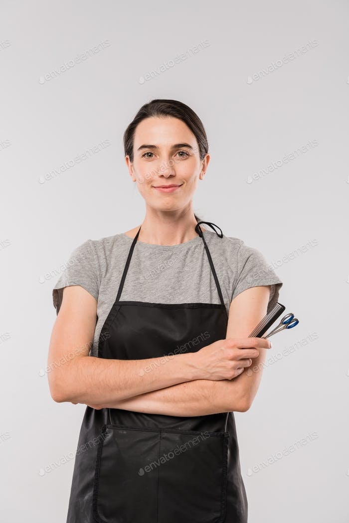 Young smiling female hairdresser in workwear holding hairbrush and scissors