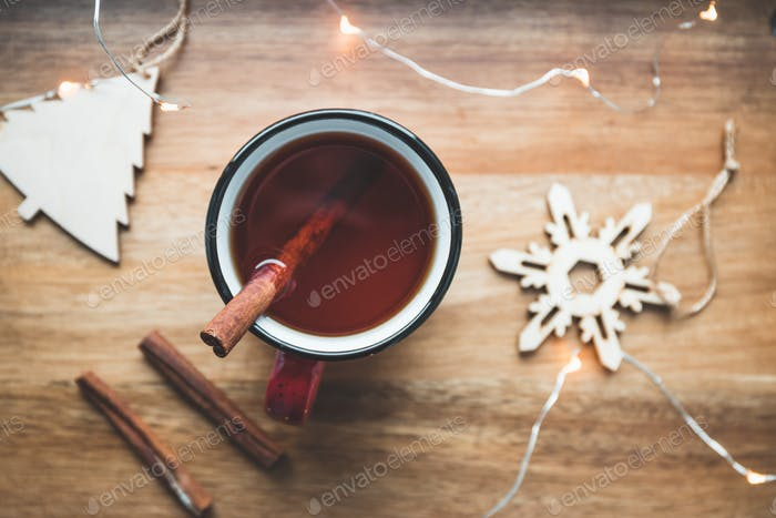 Top view of black tea with cinnamon in a red mug