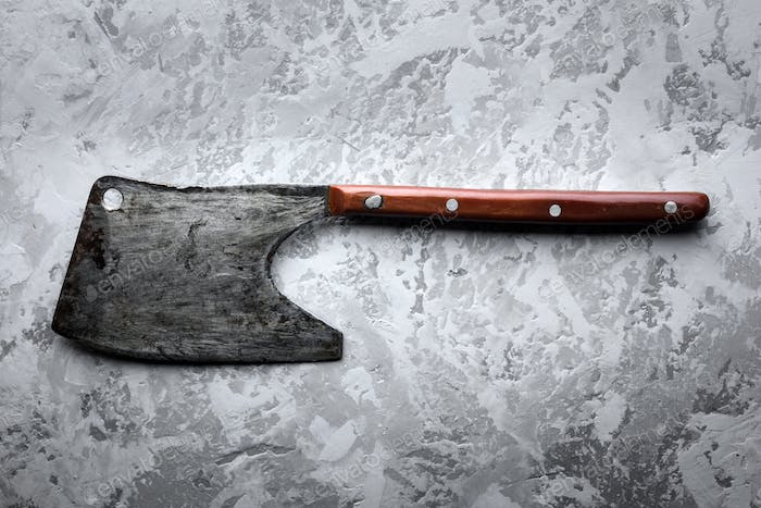 Old rustic axe for meat on grunge background