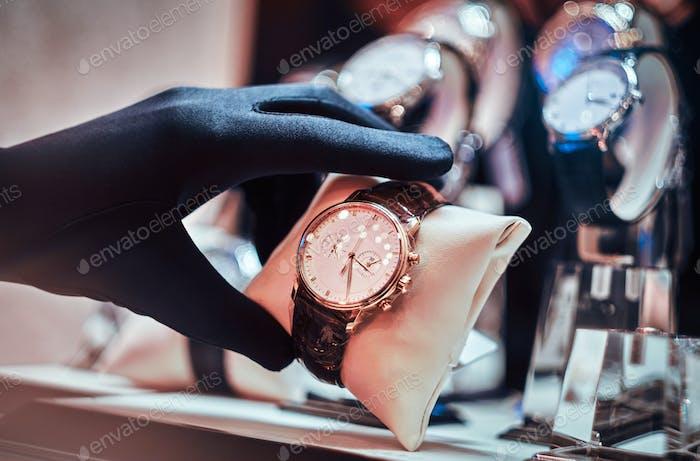 Крупным планом руки продавца в перчатках показаны эксклюзивные мужские часы из новой коллекция