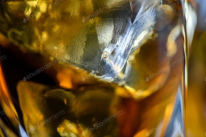 Pieces of ice cube in whiskey. Close up macro of Ice cubes in glass drink or another alcohol