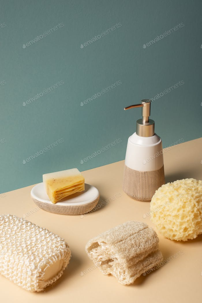 Sponges with liquid soap dispenser and soap dish on beige and grey, zero waste concept