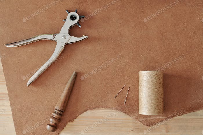 Overview of handtools and other supplies on part of beige suede