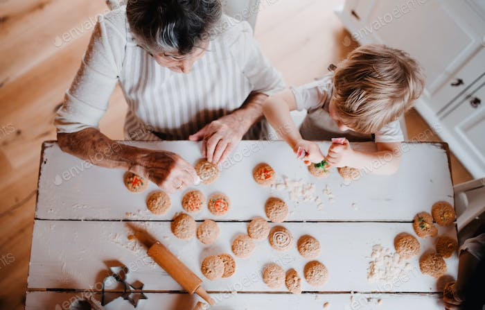 A top view of senior grandmother with small toddler boy making cakes at home.