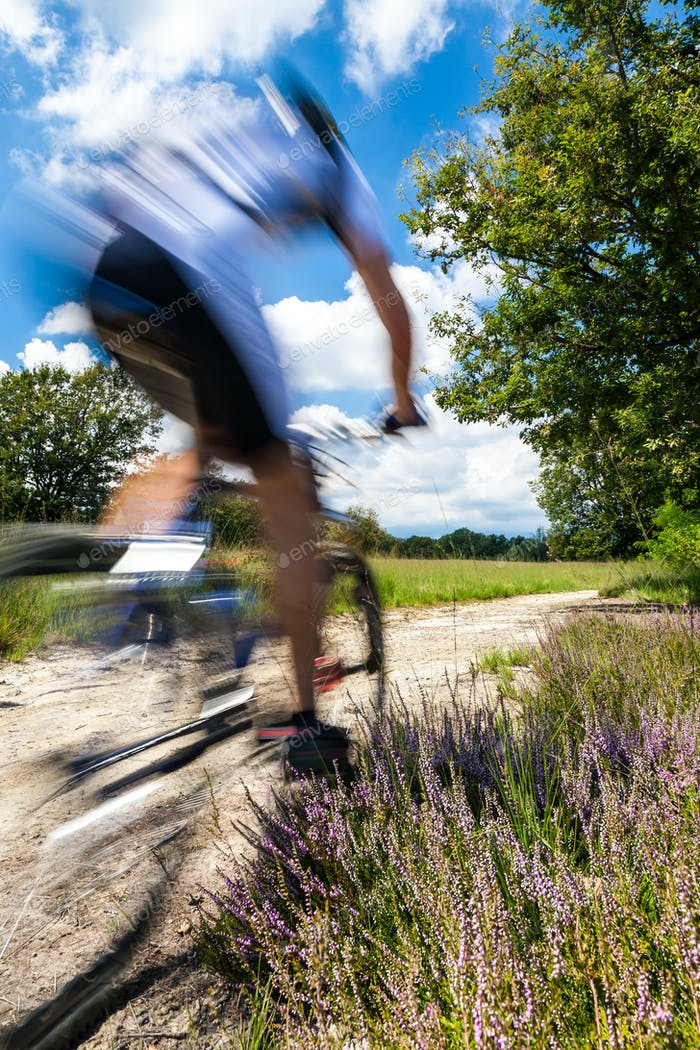 Radfahrer in verschwommener Bewegung auf einer ländlichen Straße durch grüne Frühlingswiese
