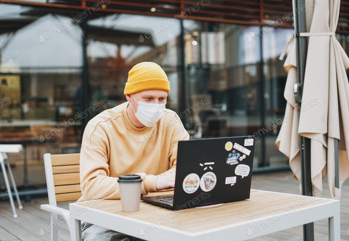 Stylish man hipster in face mask freelancer working on laptop in street cafe