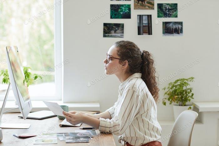 Fotografin bei der Überprüfung von Bildern am Arbeitsplatz